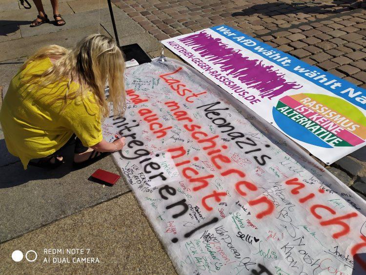 """Passantin in Chemnitz beim Unterschreiben eines Transparents """"Lasst Nazis nicht marschieren und auch nicht mitregieren"""""""